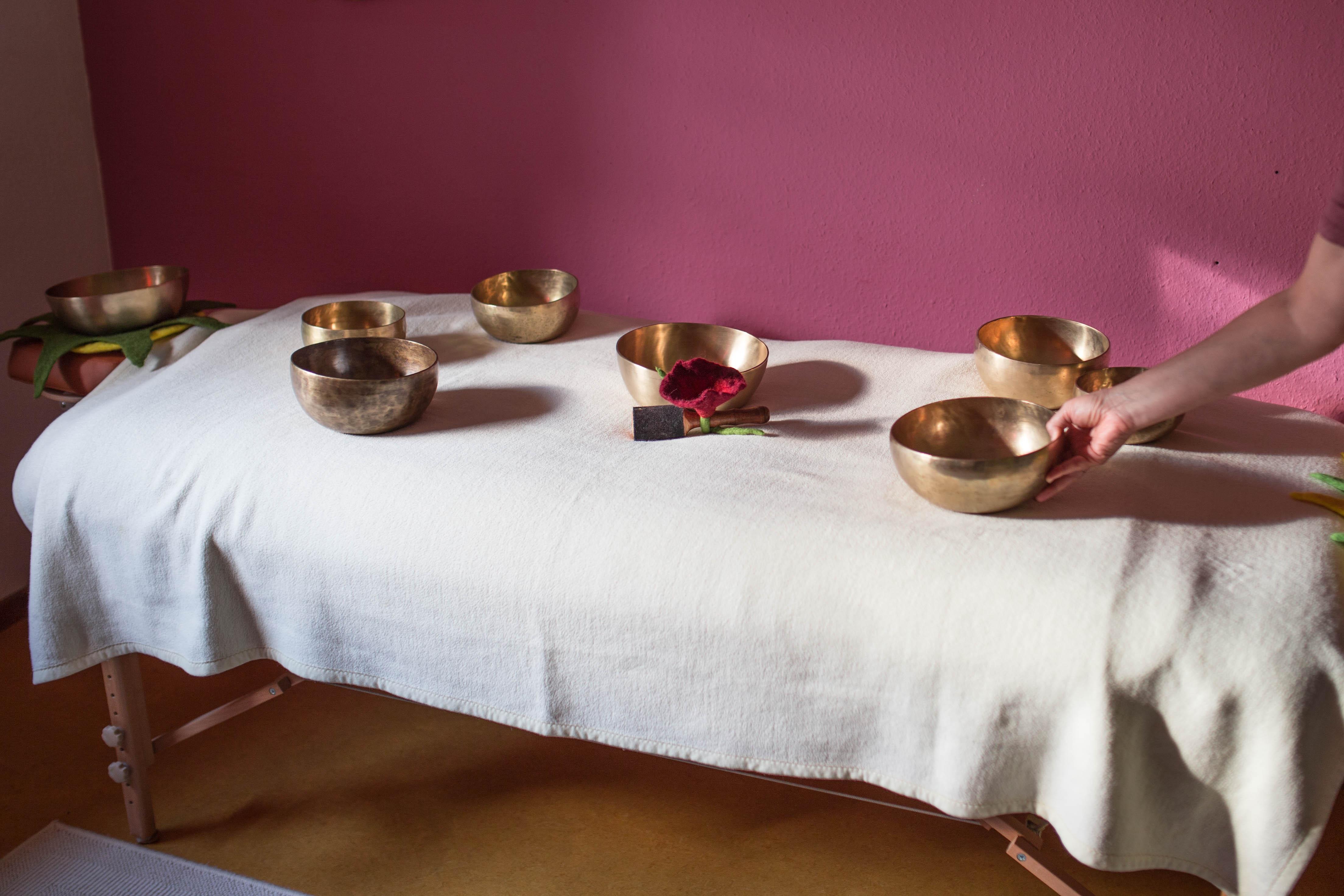 Die Massage-Liege mit Klangschalen wird für die Klangmassage vorbereitet
