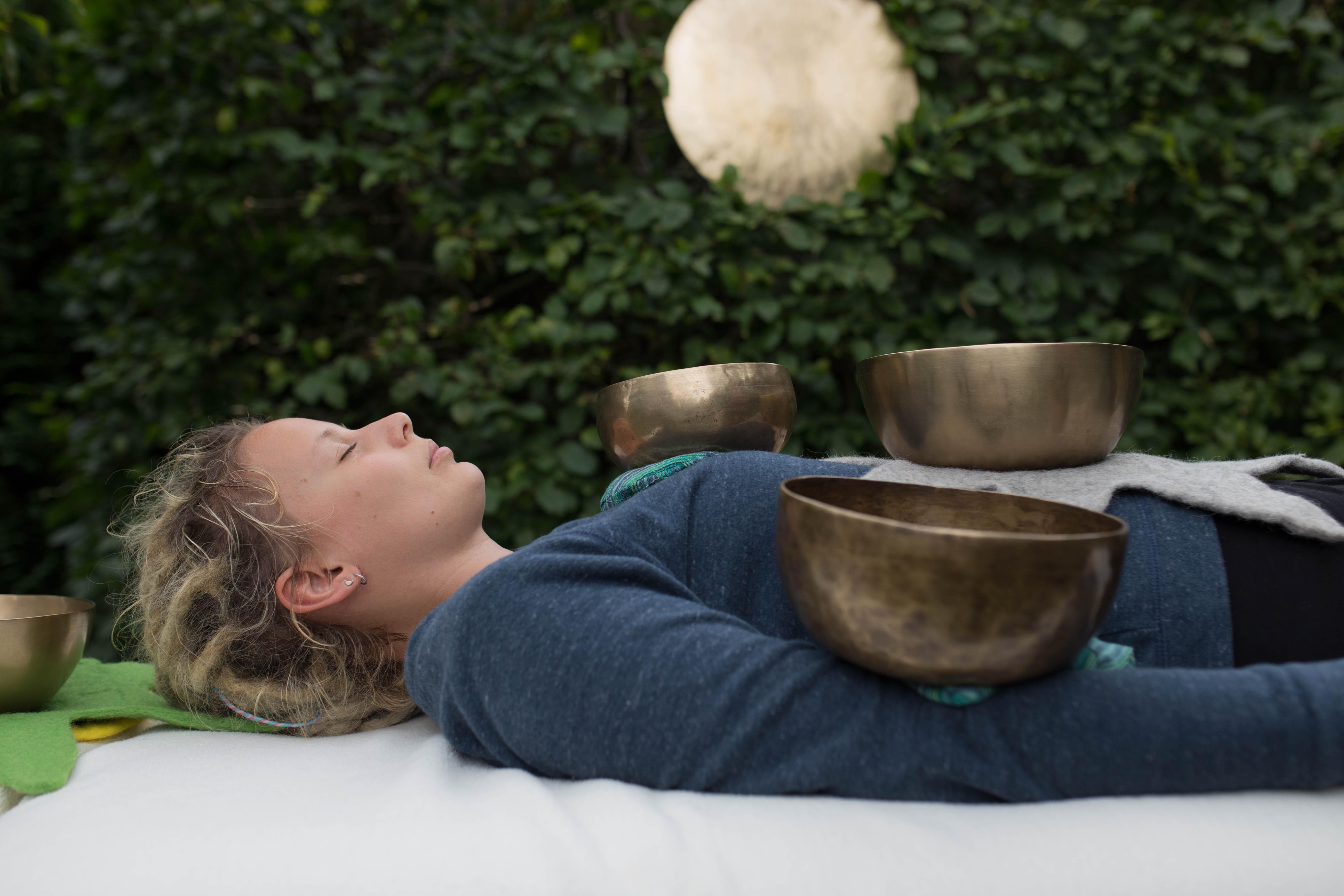Eine Kundin entspannt sich während der Klangmassage